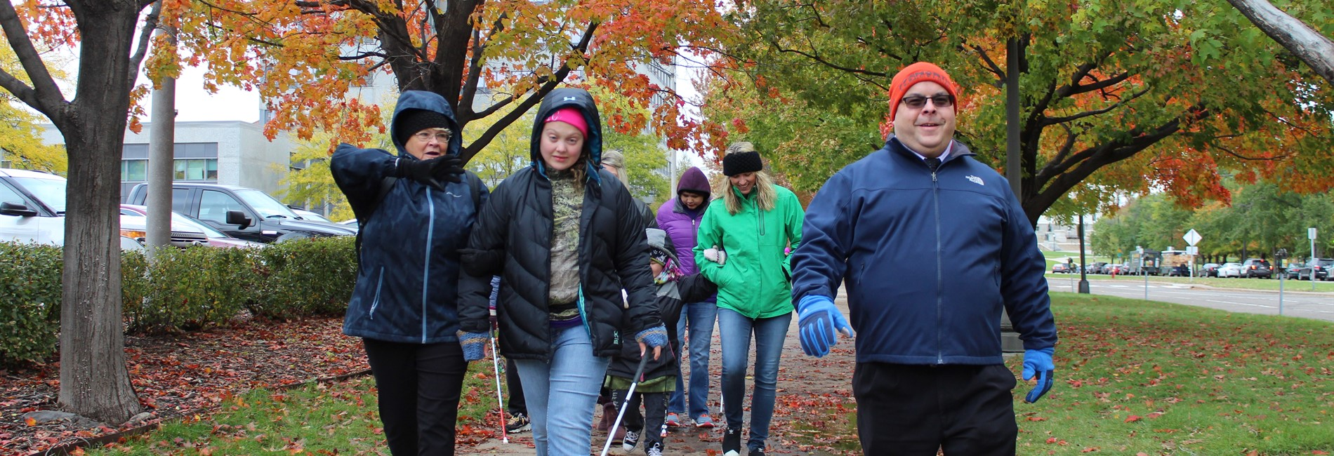 A group of people using white canes walking down a sidewalk with fall foliage in the background
